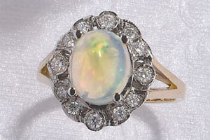The Heritage Collection: Large, lustrous opal set in a diamond and 18ct gold cluster ring