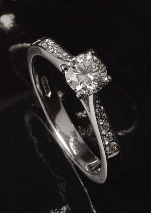 Solitaire diamond ring with two lines of shoulder diamonds